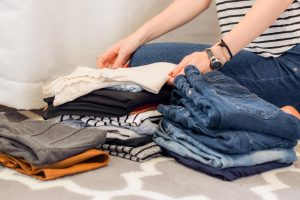 avoid unwanted moving expenses- a girl folding clothes