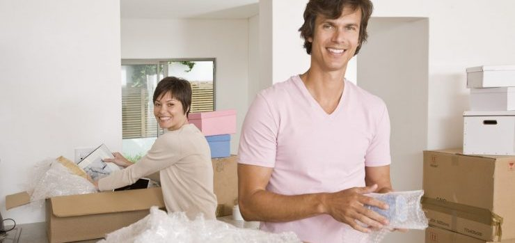 Couple unpacking dishes in kitchen