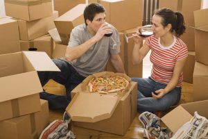 pack an essentials box - a couple with a moving boxes and pizza