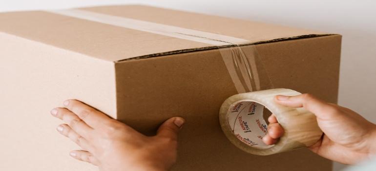 man taping the moving box