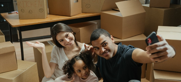 Parents and daughter taking a photo in front of moving boxes