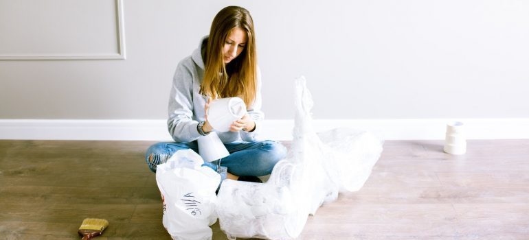 Woman unpacking to make her house a home and deal with homesickness after moving easier
