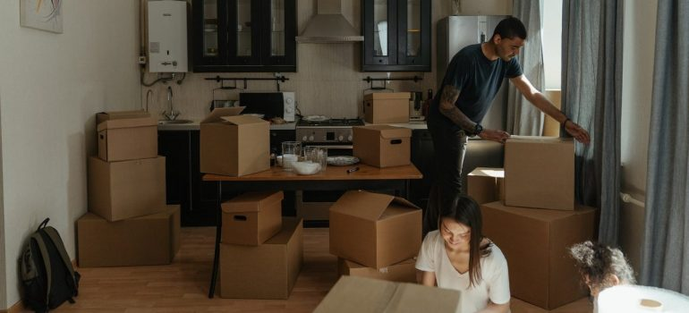 a husband moving boxes around the kitchen while his wife is handling a box on the floor