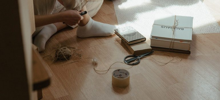 a woman sitting on the floor with scissors, tape and small rope for packing and moving collectibles