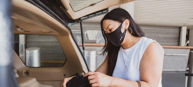 A woman unpacking her car