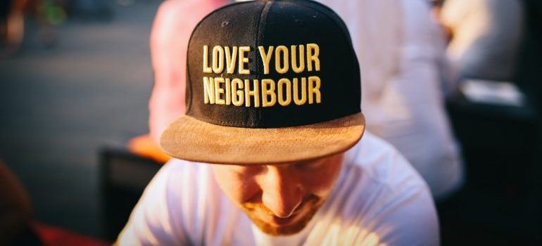 """A man with a """"love your neighbor"""" hat"""
