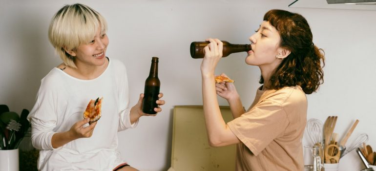 Two girls, roommates eating pizza and drinking together in their home!