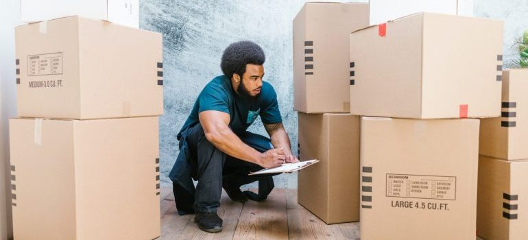 A mover working for a moving company checking on the prepared boxes for the move.