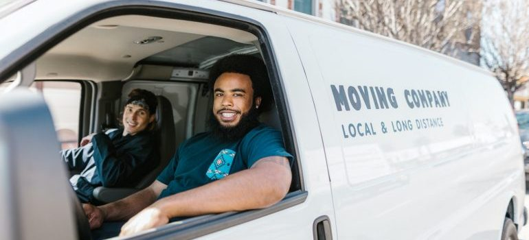 Two guys working for a moving company in a moving truck.