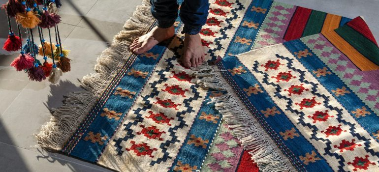 person preparing to pack and move expensive rugs