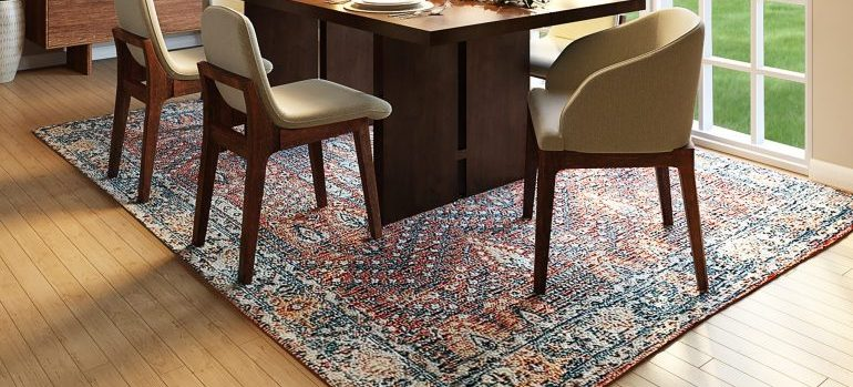 a table and chairs on a fine rug