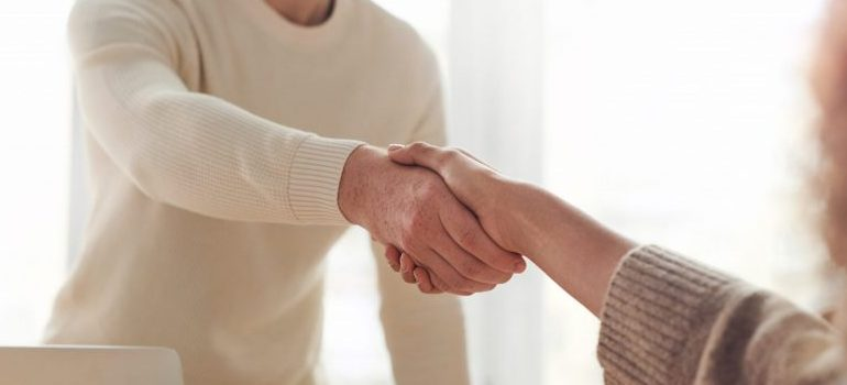 an employee of one of the moving companies California to Texas shaking hands with a customer